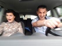 Verrückter emotionaler Mann mit einer Frau im Auto Stockbilder
