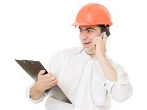 Verrückter Geschäftsmann in seinem Sturzhelm am Telefon. lizenzfreies stockfoto