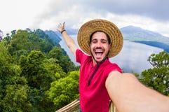 Verrückter gut aussehender Mann, der ein selfie auf einer szenischen Landschaft nimmt lizenzfreie stockbilder