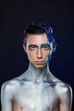 Verrückter junger androgyner Mann mit Gesichtskunst raumfahrer Ungewöhnliche Person stockbild