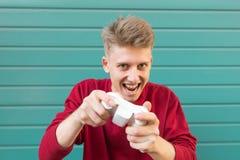 Verrückter junger Gamer in einem roten Sweatshirt und in einem Steuerknüppel in seiner Hand, Konsolenspiele spielend stockbilder