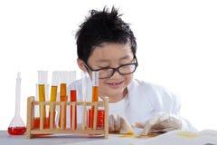 Verrückter kleiner Wissenschaftler mit flüssiger Chemie stockfotografie