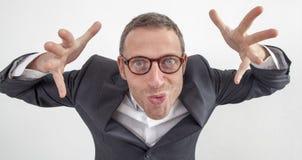 Verrückter Manager, der mit den Händen für erschreckenden oder drohenden Angestellten spielt Stockbilder