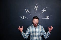 Verrückter Mann, der unter gezogenen Blitzen über Tafel schreit und steht Stockfotos