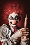 Verrückter medizinischer Clown, der übergroße Spritze hält Stockfotos