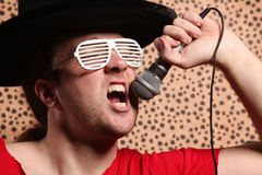 Verrückter Rock- und Rollensänger mit einem großen schwarzen Hut, Parteigläser vor einem Gepard enthäuten Hintergrund Lizenzfreie Stockbilder