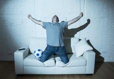 Verrücktes Fußballfan, das Fernsehfußballspiel allein, aufpasst glückliches feierndes Ziel zu schreien stockfotografie
