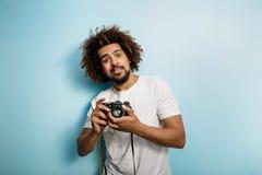 Verrassend neemt het kijken krullend-geleide donkerbruine mens een foto Ouderwetse camera in de handen Een joyous fotograaf stock fotografie