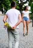 Verrassing voor haar De mensenhuiden bloeien boeket achter rug terwijl meisjes romantische datum wacht Paarvergadering voor datum royalty-vrije stock fotografie