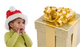 Verrast babymeisje met één gift van Kerstmis Stock Afbeeldingen