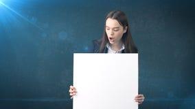 Verrast Bedrijfsvrouwenportret met lege witte raad op geïsoleerd blauw Vrouwelijk model met lang haar Royalty-vrije Stock Afbeelding