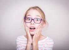 Verrast of geschokt gezicht van kindmeisje in violette glazen Royalty-vrije Stock Afbeeldingen