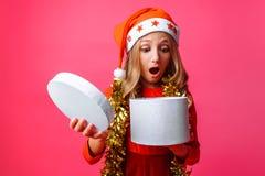 Verrast meisje in Kerstmanhoed en met klatergoud rond haar halstiener stock afbeelding