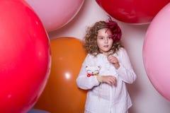 Verrast meisje met een zacht die stuk speelgoed door reusachtige ballons wordt omringd Royalty-vrije Stock Afbeelding