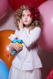 Verrast meisje met een zacht die stuk speelgoed door reusachtige ballons wordt omringd Royalty-vrije Stock Afbeeldingen