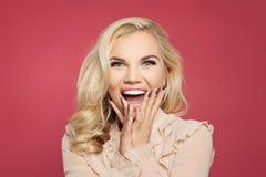 Verrast meisje met geopende mond Jonge gelukkige opgewekte vrouw die op roze lachen stock fotografie
