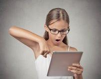 Verrast meisje met glazen die stootkussencomputer met behulp van Stock Foto