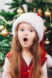 Verrast meisje in rode Kerstmishoed Stock Foto