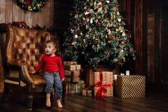 Verrast opgewekt meisje in een leunstoel tegen de achtergrond van een Kerstboom royalty-vrije stock fotografie