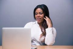 Verraste Afrikaanse onderneemster die laptop met behulp van Royalty-vrije Stock Foto