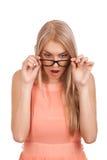 Verraste blonde vrouw die onderaan over glazen kijken Royalty-vrije Stock Afbeelding