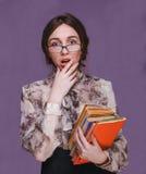Verraste de donkerbruine leraar van de meisjesvrouw in glazen met boeken open Royalty-vrije Stock Afbeeldingen