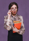 Verraste de donkerbruine leraar van het vrouwenmeisje in glazen met boeken open Stock Foto's
