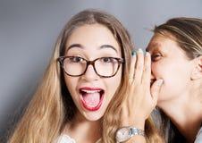 Verraste die vrouw voor een geheim aan het oor wordt verteld royalty-vrije stock fotografie