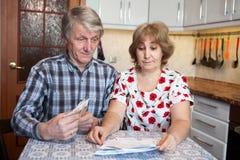 Verraste echtgenoot en vrouw die rekeningen met contant geldgeld bekijken in handen, binnenlandse keuken Royalty-vrije Stock Foto
