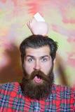 Verraste gebaarde mens met roze ceramisch spaarvarken op hoofd Stock Foto
