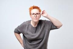 Verraste gefrustreerde rijpe vrouw met rood haar Zij heeft problemen met zicht stock foto's