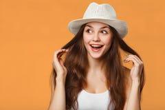 Verraste gelukkige mooie vrouw die die zijdelings in opwinding kijken, op oranje achtergrond wordt geïsoleerd stock afbeeldingen