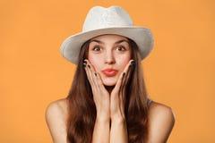 Verraste gelukkige mooie vrouw die zijdelings in opwinding kijken Opgewekt die meisje in hoed, op oranje achtergrond wordt geïsol Stock Fotografie