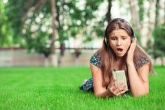 Verraste geschokte jonge vrouw die telefoon bekijken stock afbeeldingen