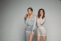 Verraste Glamrousmeisjes in glanzende kleding het bekijken camera stock afbeelding