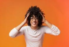 Verraste jonge krullend-haired zwarte kerel die zijn hoofd clutching, royalty-vrije stock afbeeldingen