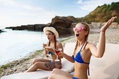 Verraste jonge mooie meisjes die op chaises dichtbij overzees liggen Stock Foto
