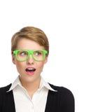Verraste jonge vrouw die in groene glazen exemplaarruimte bekijken. Stock Afbeeldingen