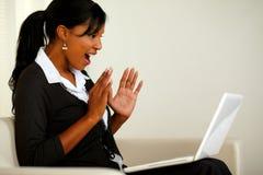 Verraste jonge vrouw die groot nieuws op laptop leest Stock Foto