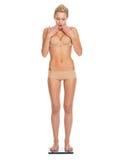 Verraste jonge vrouw in lingerie die zich op schalen bevinden Royalty-vrije Stock Afbeelding