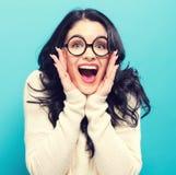 Verraste jonge vrouw op een heldere achtergrond Stock Fotografie
