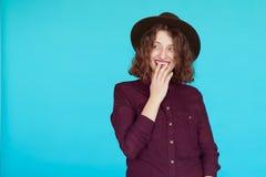 Verraste jonge vrouw over blauwe turkooise achtergrond Stock Foto
