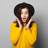 Verraste jonge vrouw over grijze achtergrond Royalty-vrije Stock Afbeelding