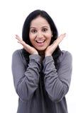 Verraste jonge vrouw tegen witte achtergrond Stock Fotografie