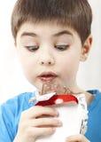 Verraste jongen met chocolade Stock Afbeelding