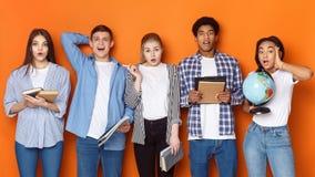 Verraste klasgenoten die met boeken camera over achtergrond bekijken royalty-vrije stock afbeeldingen