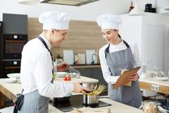 Verraste kokende deskundige die jonge kok controleren stock afbeelding