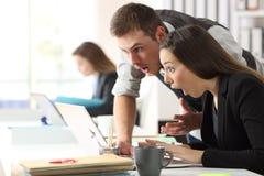 Verraste medewerkers die online nieuws lezen op kantoor royalty-vrije stock afbeeldingen