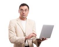 Verraste mens die kostuum en glazen met laptop dragen Stock Afbeelding