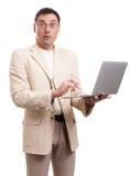 Verraste mens die kostuum en glazen met laptop dragen Royalty-vrije Stock Foto